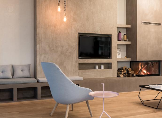 Phòng khách với gam màu trắng nhẹ nhàng làm nổi bật kệ trang trí làm từ gỗ nâu.